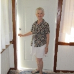 Nancyann stands by a door, ajar.