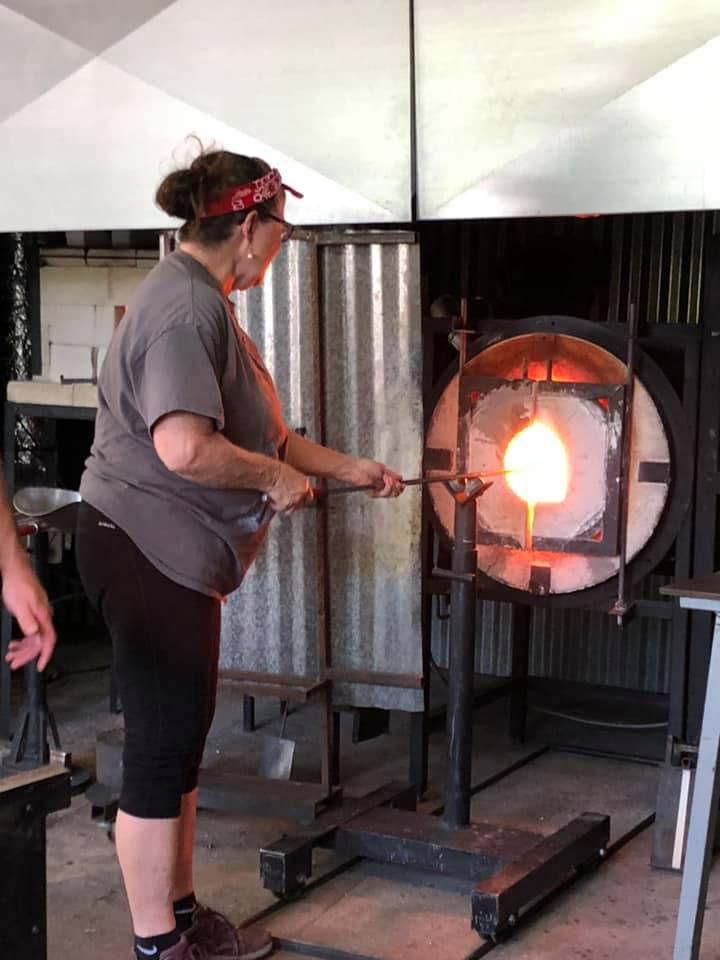 Heating the glass before blowing.